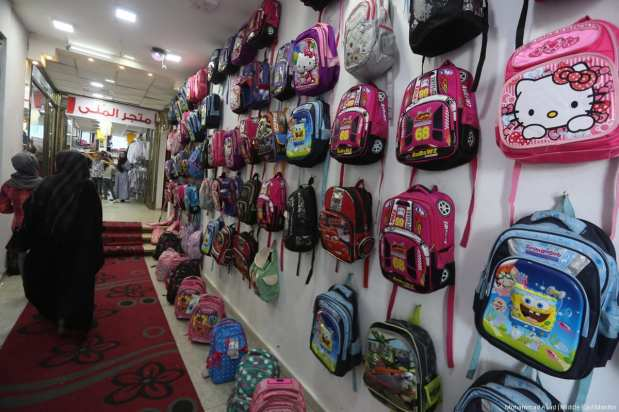 Childrens bags are made and hung ready to be purchased for the new school year. [Image: Mohammad Asad / Middle East Monitor]