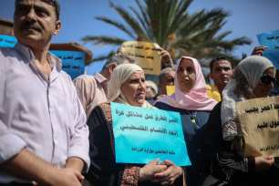 """Palestinian Ministry of Agriculture employees hold banners during a demonstration against Palestinian Government's """"obligatory and early retirement of employees"""" decision in front of the Palestinian Cabinet building in Gaza, West Bank on 12 September, 2017 [Ali Jadallah/Anadolu Agency]"""