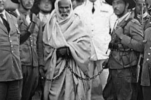 Omar al-Mukhtar is seen handcuffed and surrounded by Italian forces, and being led to the gallows.