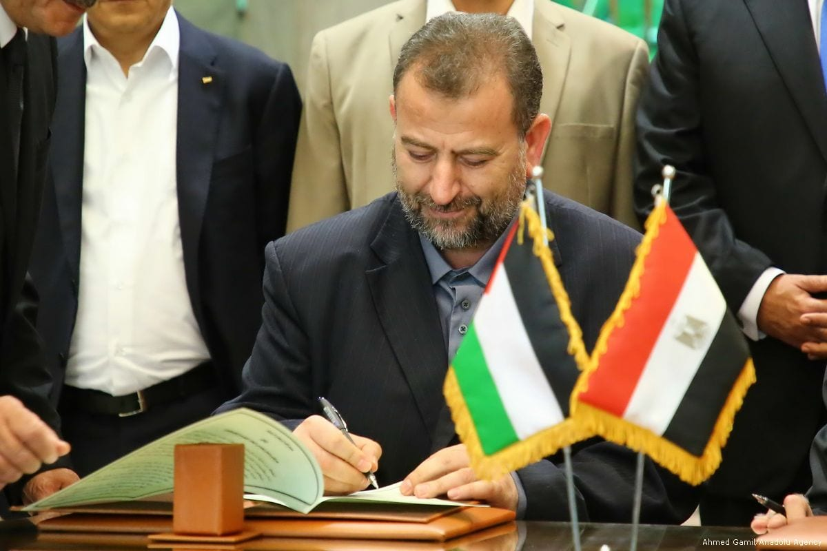 Deputy Chairman of the Movement's Political Bureau Saleh Al-Arouri signs the reconciliation agreement to build a consensus with Palestinian Fatah movement leader Azzam Al-Ahmad in Cairo, Egypt on 12 October 2017 [Ahmed Gamil/Anadolu Agency]