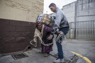 A dock worker helps a porter to load the goods on her back [Fernando Del Berro]
