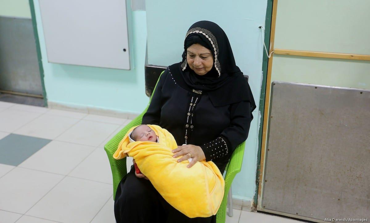 A Palestinian woman holds a newly born baby, Rami Hamdallah, named at al-shifaa hospital, in Gaza city on 2 October, 2017 [Atia Darwish/Apaimages]