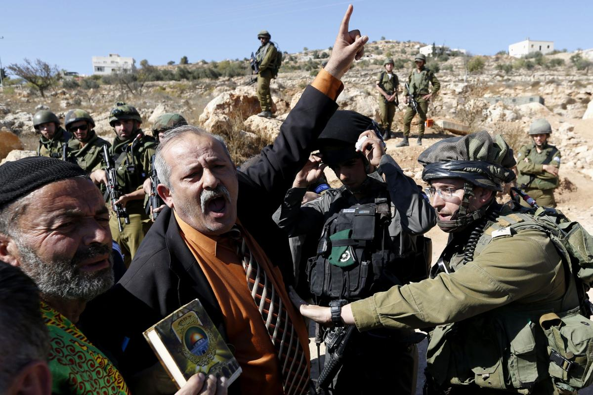 A Palestinian man shouts during a protest against closure of a road by Israeli troops south of the West Bank city of Hebron on November 10, 2017. Photo by Wisam Hashlamoun