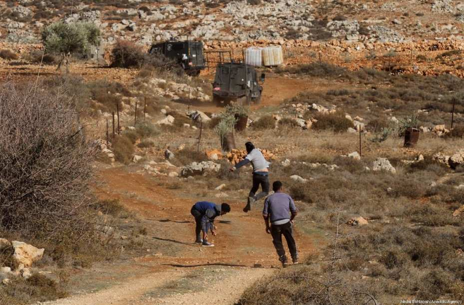 Palestinians throw stones to Israeli soldiers after a Palestinian farmer shot dead by Jewish settlers, at the Khusra village of Nablus in West Bank on November 30, 2017. After that, Palestinians detained Jewish settlers in a cave and Israeli soldiers arrived at the scene and received these detained Jewish settlers. ( Nedal Eshtayah - Anadolu Agency )