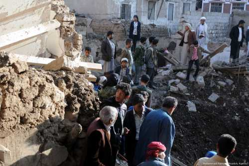People inspect the wreckage of a collapsed building after an air strike was carried out by the Saudi-led military coalition in Yemen [Mohammed Hamoud/Anadolu Agency]