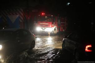 Emergency vehicles can be seen after heavy rainfall blocked roads in Gaza on 27 November 2017 [Mohammed Asad/Middle East Monitor]