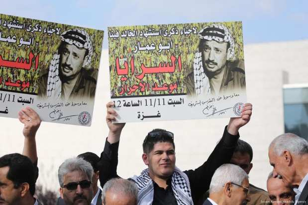 People hold portraits of the late Palestinian leader Yassir Arafat as they gather during a commemoration ceremony held for his 13th death anniversary in Ramallah, West Bank on 9 November 2017 [Issam Rimawi/Anadolu Agency]