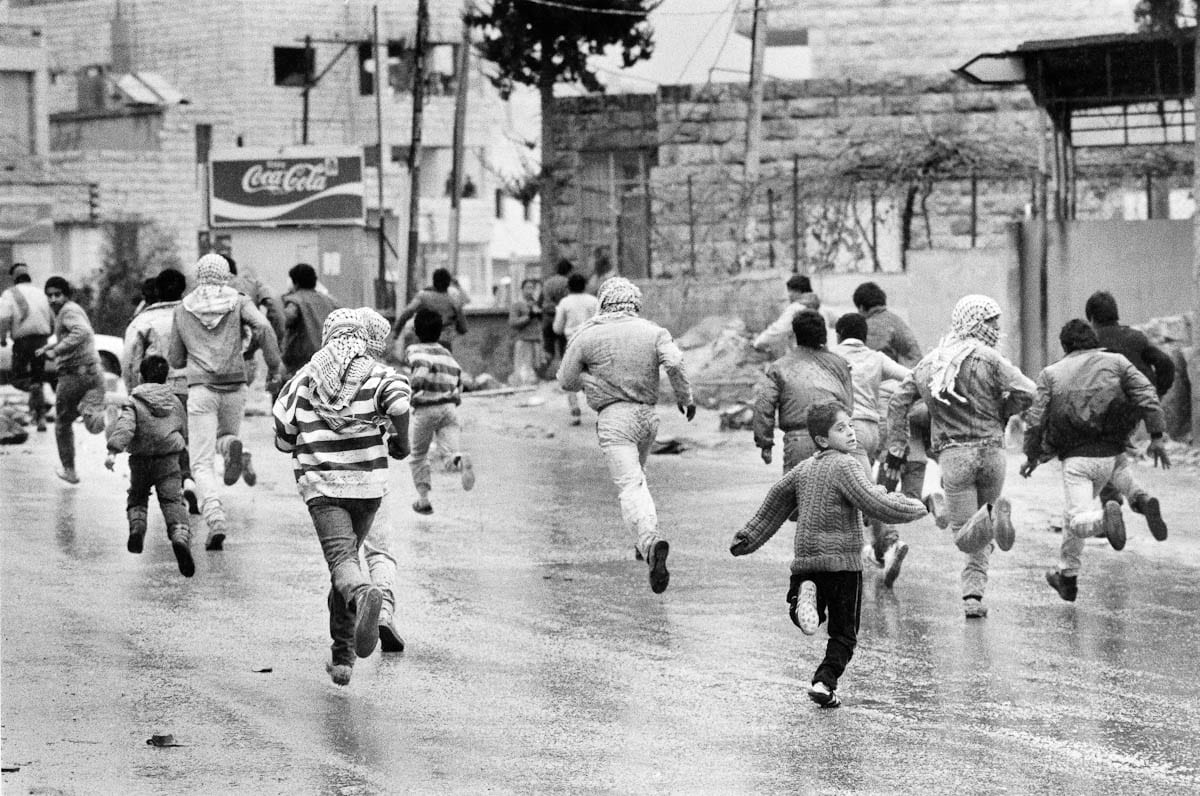 Young Palestinians run away from armed Israeli soldiers during the first Intifada. Image taken in Al Ram in the West Bank on January 1988 [Cal3b Gee / Pinterest]
