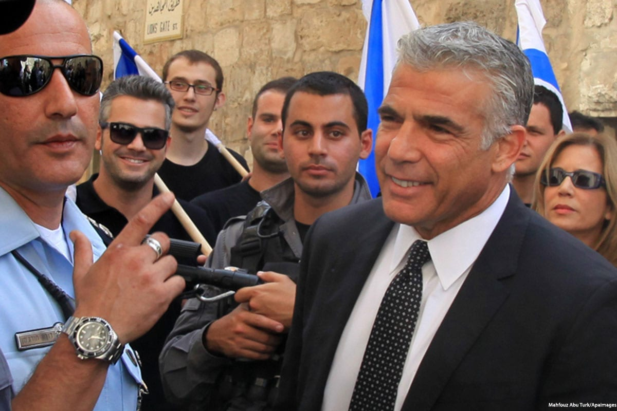 The head of Israel's opposition party, Yair Lapid (C) speaks to the press with his supporters surrounding him on 12 October 2015 [Stringer/Apaimages]