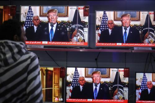Palestinians in Gaza watch as US President Donald Trump recognises occupied Jerusalem as Israel's capital on 6 December 2017. [Ali Jadallah/Anadolu Agency]