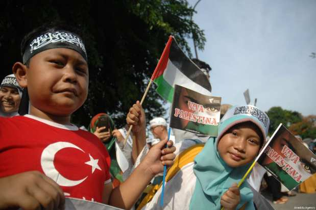 A child wearing a t-shirt with Turkish Flag as Indonesian Muslims stage a protest outside the US ambassador's office in Indonesia against US President Donald Trump's announcement to recognise Jerusalem as the capital of Israel, in Jakarta on December, 8, 2017 [Dasril Roszandi / Anadolu Agency]