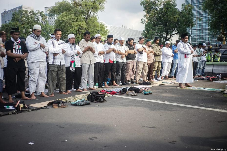 Indonesian Muslims perform Friday prayer outside the US ambassador's office in Indonesia after US President Donald Trump's announcement to recognise Jerusalem as the capital of Israel, in Jakarta on December, 8, 2017 [Anton Raharjo / Anadolu Agency]