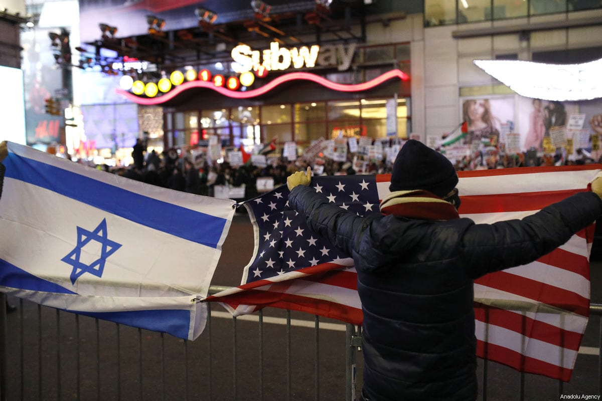 A group of pro-Israelis open both American and Israeli flags and catcall the demonstrators from across the street during a demonstration against U.S. President Donald Trump's recognition of Jerusalem as Israel's capital, at the Times Square in New York City, United States on December 09, 2017 [Atılgan Özdil / Anadolu Agency]