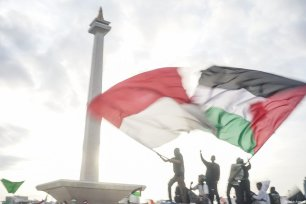 Protesters wave a Palestinian and Indonesian flags in the demonstration to support Palestine at National Monument in Jakarta, Indonesia on December 17, 2017 [Nani Afrida / Anadolu Agency]