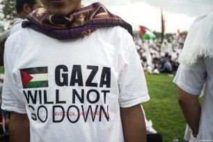"A protester wears a Palestine t-shirt ""Gaza will not go down"" in the demonstration to support Palestine at National Monument in Jakarta, Indonesia on December 17, 2017 [Nani Afrida / Anadolu Agency]"