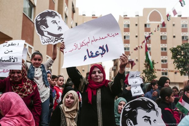 Palestinians hold placards during Qatar National Day celebrations organised by Qatari Committee for the Reconstruction of Gaza in Khan Yunis, Gaza on 19 December 2017 [Mustafa Hassona/Anadolu Agency]