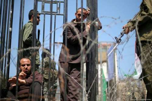 Men play the role of jailed Palestinians and Israeli soldiers during a rally in support of Palestinian prisoners on a hunger strike in Israeli jails, in Gaza City on Monday. (Mohammed Salem/Reuters)