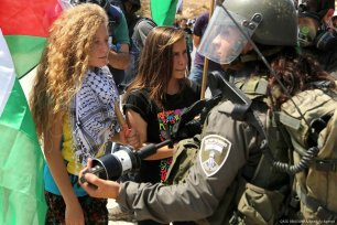Photo dated in November 2012 shows Palestinian girl Ahed al-Tamimi (C) challenging Israeli soldiers during a protest in Ramallah, West Bank [QAIS ABUSAMRA/Anadolu Agency]