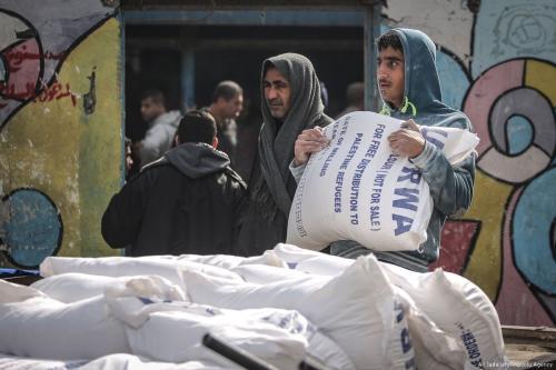 Palestinian men carry food aid given by UNRWA in Gaza City, Gaza on 15 January 2018 [Ali Jadallah/Anadolu Agency]