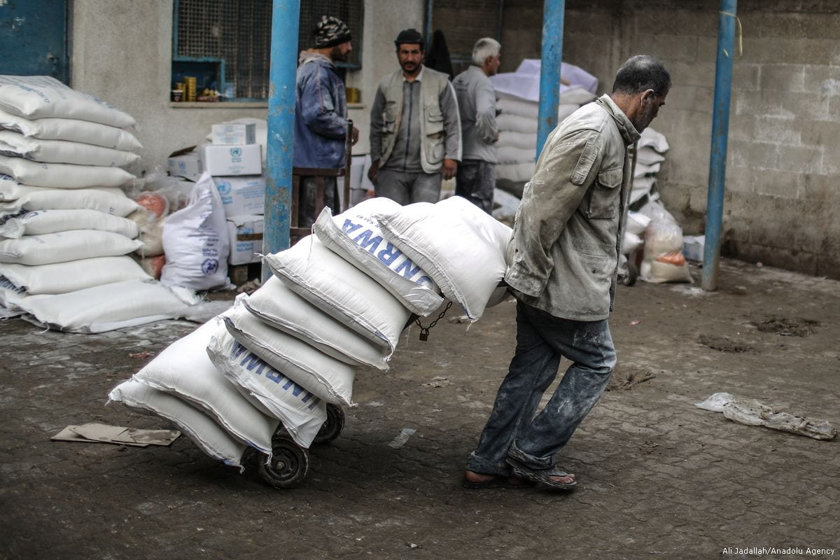 A man carries sacks of flours during a food aid distribution by the United Nations Relief and Works Agency for Palestine Refugees in the Near East (UNRWA) at Al-Shati Refugee Camp in Gaza City, Gaza on January 15, 2018 [Ali Jadallah / Anadolu Agency]