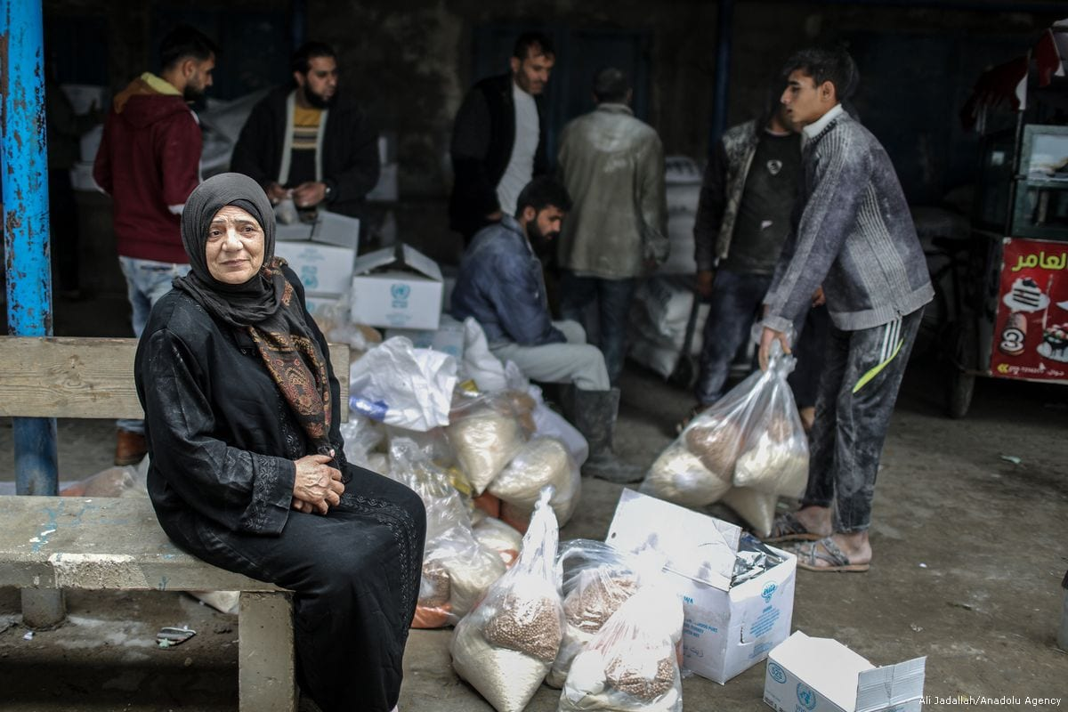 A woman waits during a food aid distribution by the United Nations Relief and Works Agency for Palestine Refugees in the Near East (UNRWA) at Al-Shati Refugee Camp in Gaza City, Gaza on 15 January 2018 [Ali Jadallah/Anadolu Agency]
