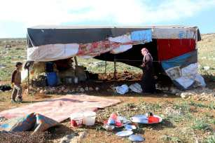 A Syrian mother and her child are seen outside a makeshift home in a refugee camp that hosts displaced Syrians [Muhammed Abdullah/Anadolu Agency]