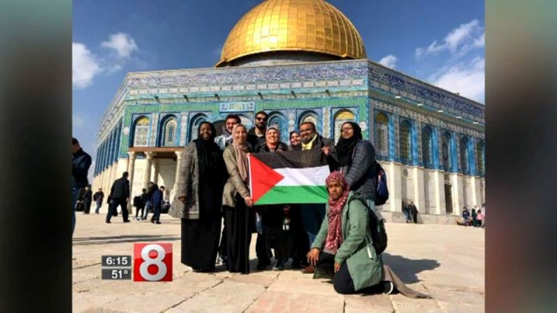 Members of a Connecticut church's interfaith group hold the Palestinian flag in fron of the Dome of the Rock in early January 2018 [Screengrab / News8 / wtnh.com]