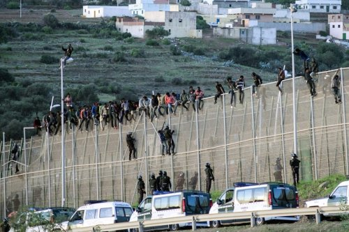 African migrants sit atop a border fence, as Spanish Civil Guard officers stand underneath, during an attempt to cross into Spanish territories, between Morocco and Spain's north African enclave of Melilla on October 16, 2014 [Reuters]