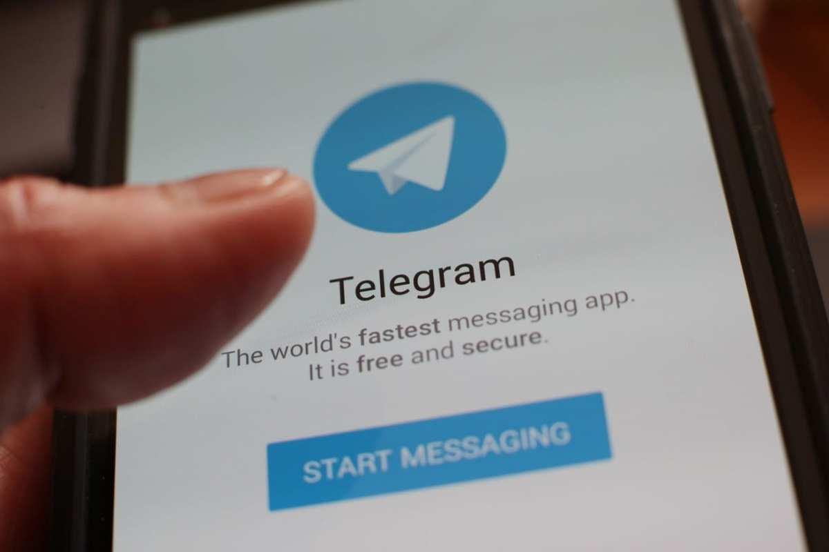 A user loads the Telegram app on their phone [Yui Mok / PA]