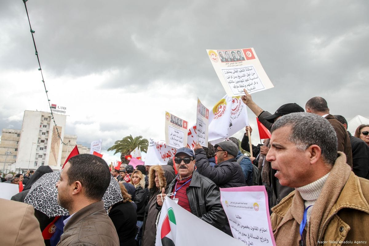 Tunisian academicians hold placards during a protest demanding higher wages in front of parliamentary building in Tunis, Tunisia on 21 February 2018 [Nacer Talel/Anadolu Agency]