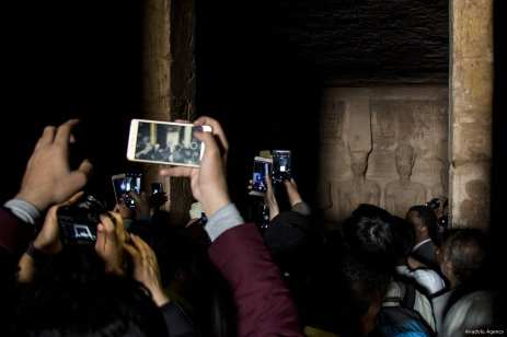 Visitors take photos as sunbeams light up the statues of King Ramesses II at Abu Simbel in Aswan, Egypt on 22 February 2017 [İbrahim Ramadan/Anadolu Agency]