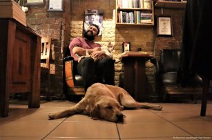 A visitor strokes a cat as a dog sleeps on the ground at a cafe belonging to Turkish man Suat Kilic who allows stray animals to enter his cafe [Mustafa Ünal Uysal/Anadolu Agency]