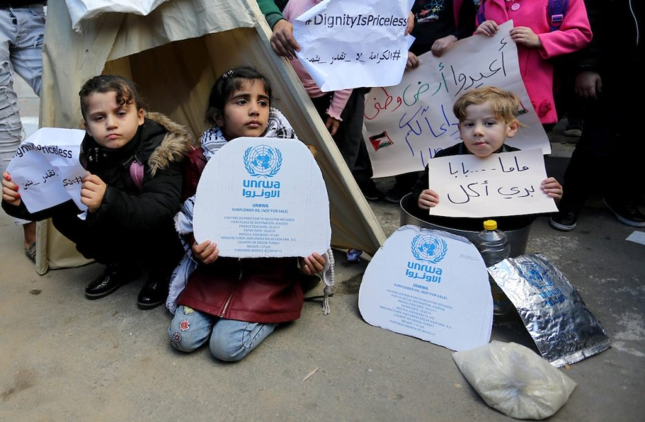 Palestinian school students shout slogans and hold placards in a protest against the US move to freeze funding for the UN agency for Palestinian refugees on 31 January, 2018 at the al-Nusairat refugee camp, in central Gaza Strip [Ashraf Amra/Apaimages]