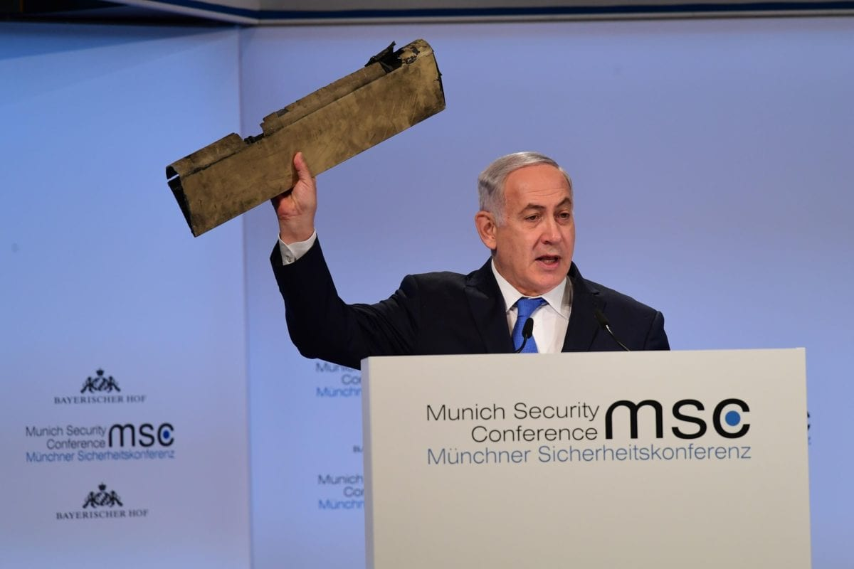 Israel's Prime Minister Benjamin Netanyahu holds up a piece of wreckage he claims is from an Iranian drone that was shot down by Israel on February 10, at the 54th Munich Security Conference (MSC) in Germany on 18 February, 2018 [Andreas Gerbert/Anadolu Agency]