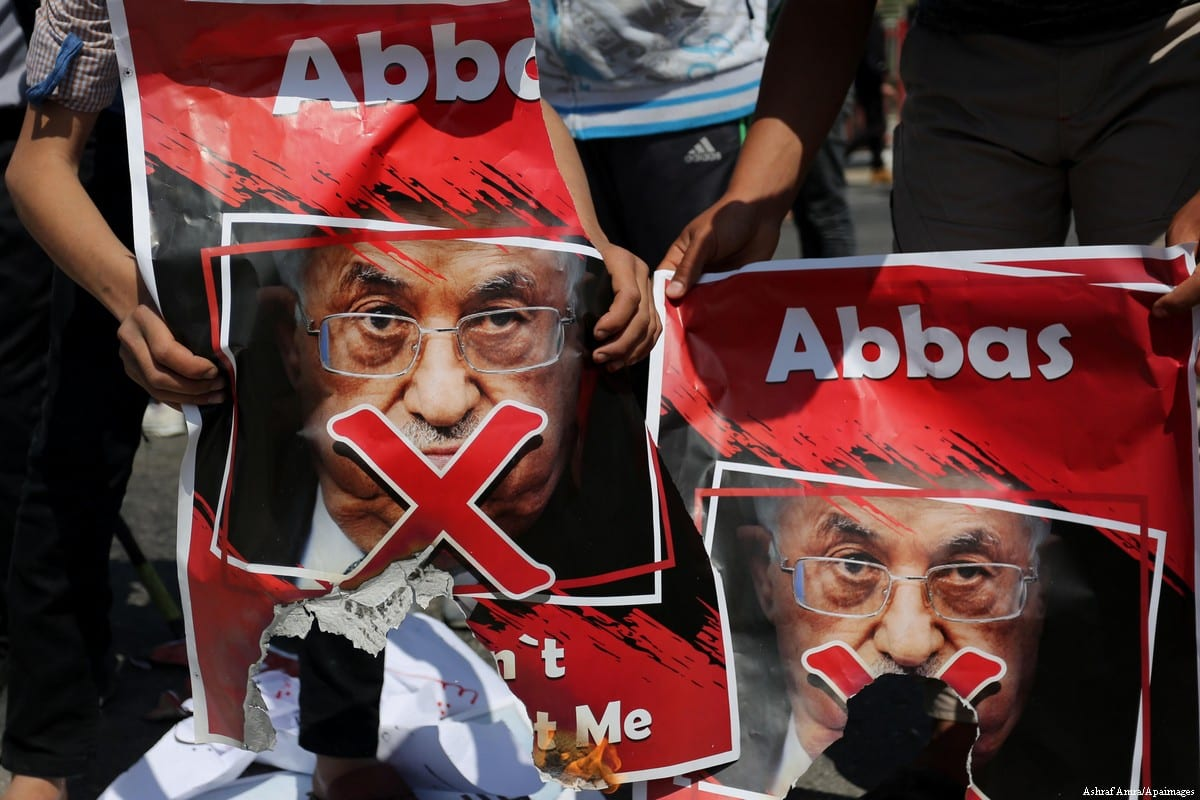 Hamas supporters carry posters depicting Palestinian President Mahmoud Abbas with a red cross during a protest in Gaza [Ashraf Amra/Apaimages]