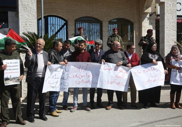 Palestinians hold placards demanding the closure of the American security, political, cultural and economic representations in front of America House in Ramallah, West Bank on 28 February 2018. [Issam Rimawi/Anadolu Agency]