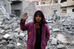 "DAMASCUS, SYRIA - MARCH 02: A Syrian girl raises her hand as she poses for a photo for the awareness-raising campaign ""#Iamstillalive"" on the social media, organized by activists and children, demanding support for the humanitarian crisis caused by Assad Regime and its supporters in Eastern Ghouta of Damascus, Syria on March 02, 2018. ( Amer Alshami - Anadolu Agency )"
