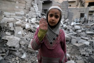 """DAMASCUS, SYRIA - MARCH 02: A Syrian girl raises her hand as she poses for a photo for the awareness-raising campaign """"#Iamstillalive"""" on the social media, organized by activists and children, demanding support for the humanitarian crisis caused by Assad Regime and its supporters in Eastern Ghouta of Damascus, Syria on March 02, 2018. ( Amer Alshami - Anadolu Agency )"""