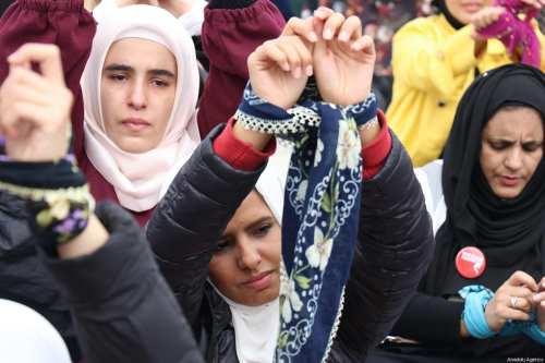 Women of International Conscience Convoy comprising people from over 50 countries, tie their hands to attract notice to Syrian women in prisons, as they gather at a fair area after their arrival in Hatay, Turkey on March 8, 2018 [Erdal Türkoğlu / Anadolu Agency]
