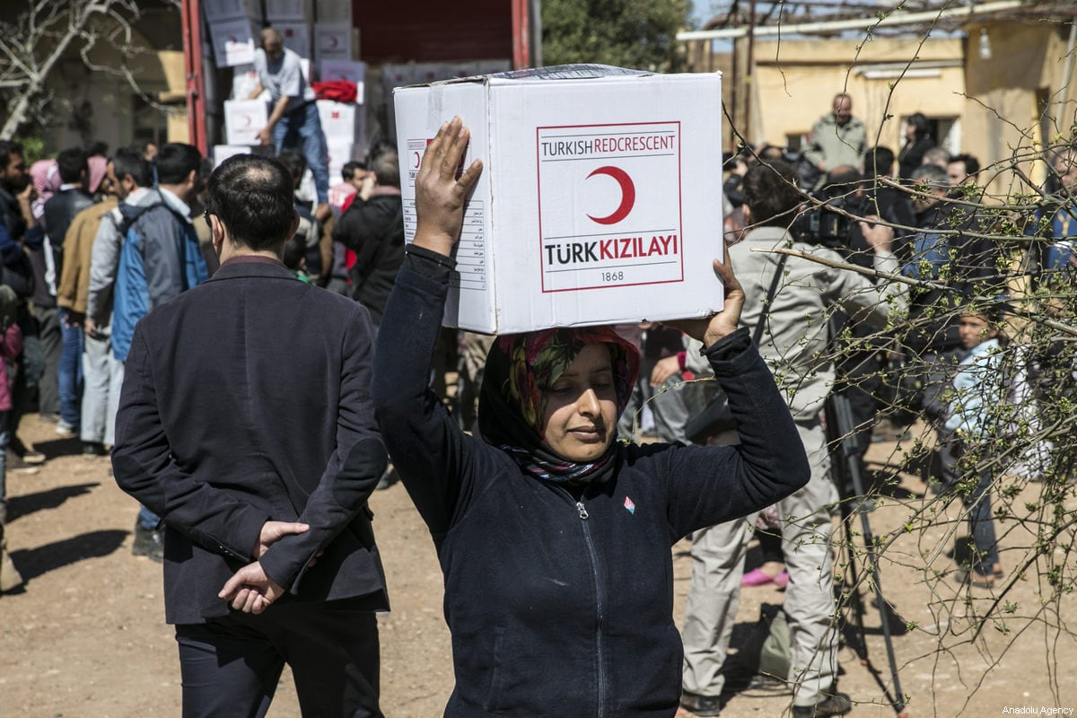 """Turkish Soldiers and Turkish Red Crescent members distribute humanitarian aid to Syrian families after clearing Deir Ballut village of Jinderes, from PYD/PKK-Daesh terrorists in Afrin, Syria, within """"Operation Olive Branch"""" on 9 March, 2018 [Cem Genco/Anadolu Agency]"""