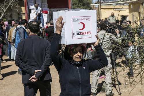 "Turkish Soldiers and Turkish Red Crescent members distribute humanitarian aid to Syrian families after clearing Deir Ballut village of Jinderes, from PYD/PKK-Daesh terrorists in Afrin, Syria, within ""Operation Olive Branch"" on 9 March, 2018 [Cem Genco/Anadolu Agency]"
