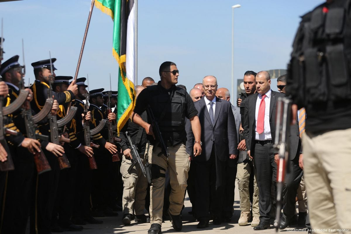 Palestinian Prime Minister Rami Hamdallah seen in the centre surrounded by his security team after an explosive was set off aimed at his convoy, in Gaza on 13 March 2018 [Mohammed Asad/Middle East Monitor]