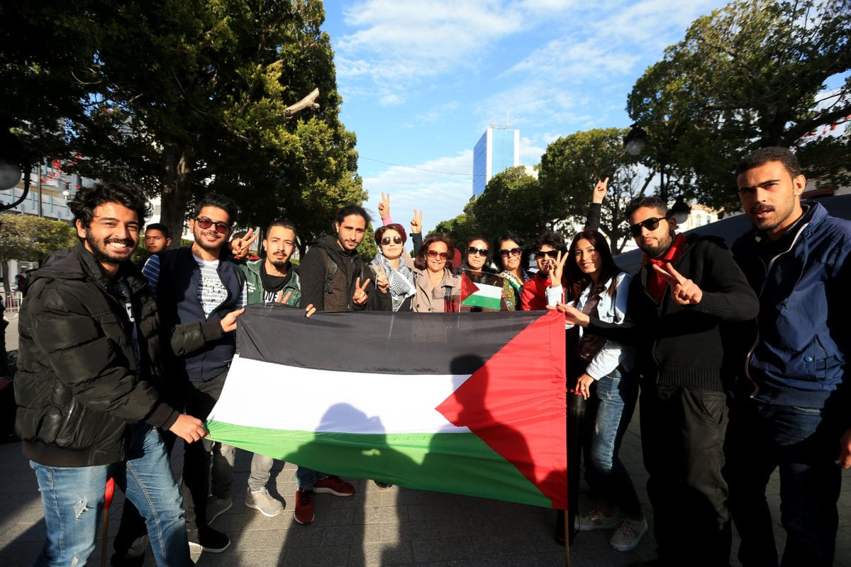 People pose for a photo with a Palestinian flag during a demonstration marking the 'Palestinian Land Day' at the Habib Bourguiba Avenue in Tunis, Tunisia on March 31, 2018. [Yassine Gaidi/Anadolu Agency]
