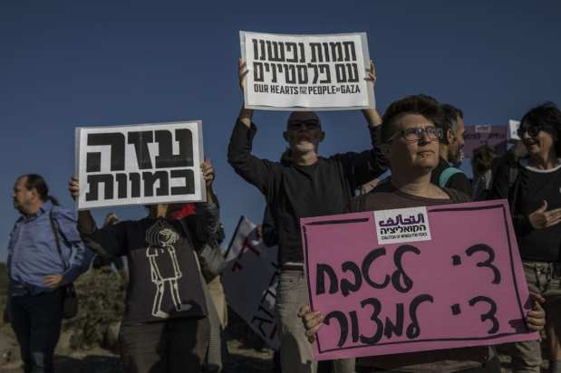 "Members of ""Coalition of Women for Peace"" consisting Israeli and Palestinian activists hold banners during a protest held to support the ""Great March of Return"" near the Gaza border in Sderot, Israel on 31 March, 2018. [Stringer/Anadolu Agency]"