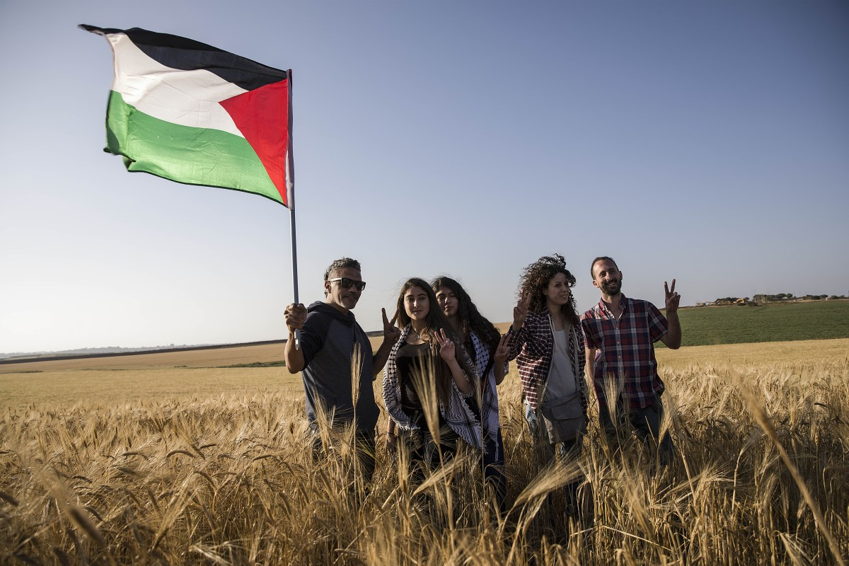 "Members of ""Coalition of Women for Peace"" consisting Israeli and Palestinian activists hold a Palestinian flag during a protest held to support the ""Great March of Return"" near the Gaza border in Sderot, Israel on 31 March, 2018 [Stringer/Anadolu Agency]"