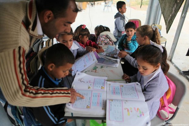 Students have their lessons inside a tent after Israeli forces demolished a primary school in Hebron, West Bank on 11 April 2018 [Mamoun Wazwaz/Anadolu Agency]