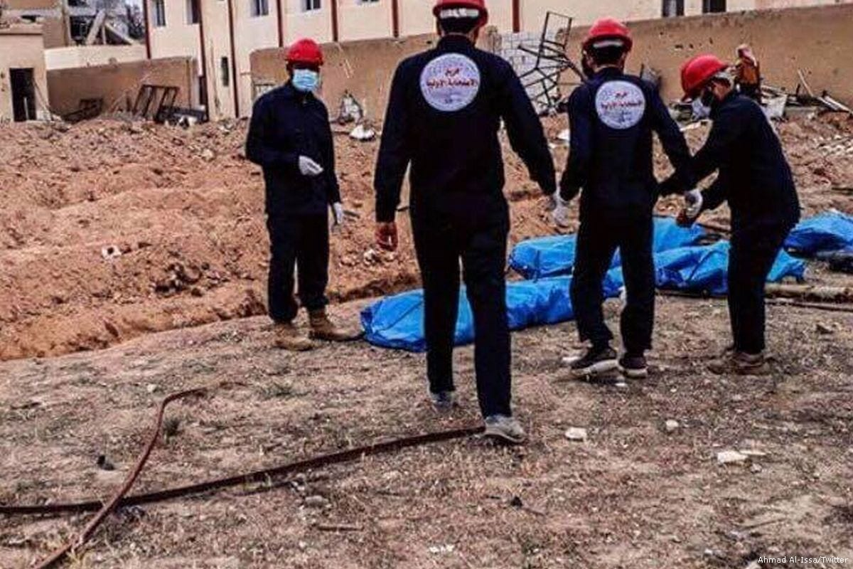 Syrians remove the bodies that were found in mass graves in Raqqa, Syria [Ahmad Al-Issa/Twitter]