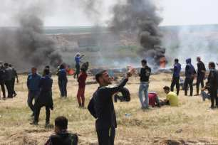 Palestinian protesters take cover after Israeli forces fire at Palestinian protesters during the 'Great March Of Return' on 6th April 2018 [Mohammed Asad/Middle East Monitor]