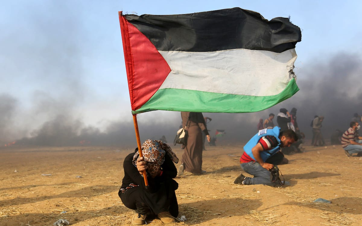 A Palestinian protester takes cover after Israeli forces attacked protesters during the 70th anniversary of the Nakba, at the Israel-Gaza border on 15 May, 2018 [Ashraf Amra/Apaimages]