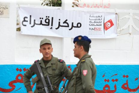 A banner is seen as Tunisian security officers stand guard at a polling station during Tunisian local elections, which was held first time after 2011 Arab Spring revolution, in Ben Arous, Tunisia on May 06, 2018 [Yassine Gaidi / Anadolu Agency]